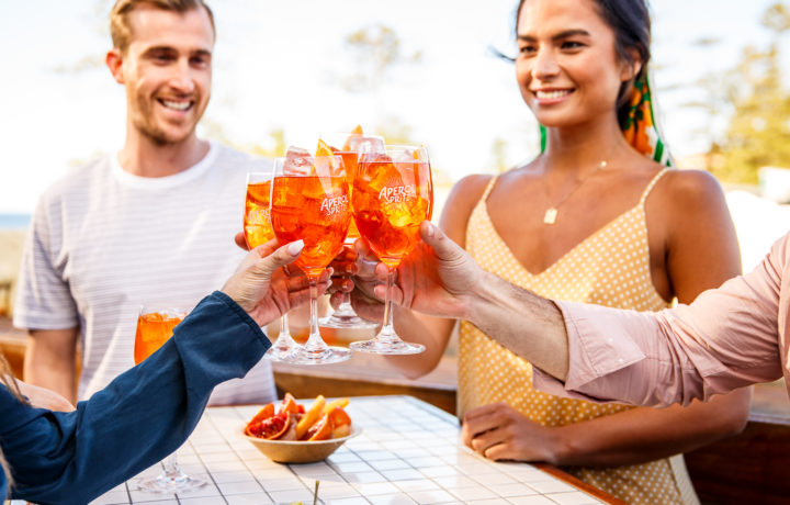 Happy people cheers with Aperol Spritz